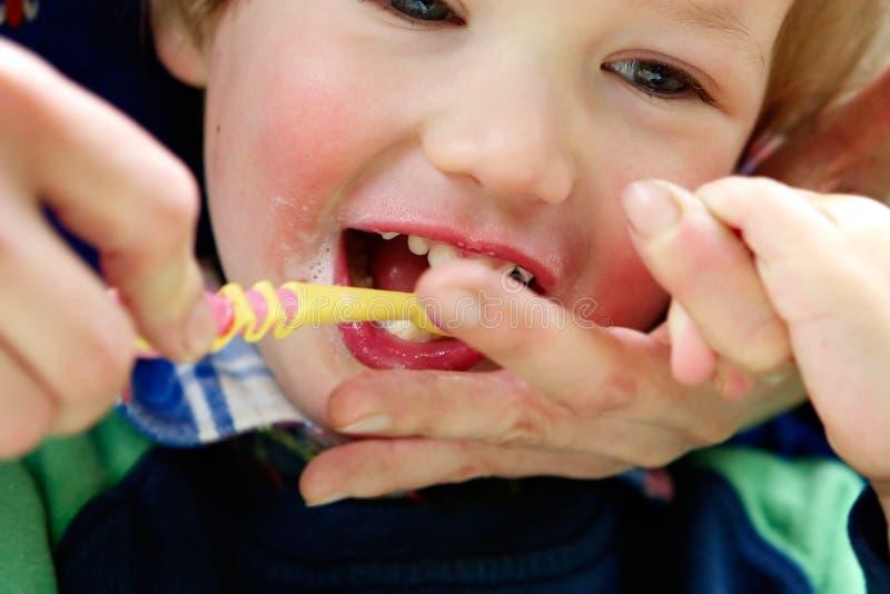 Het kind maakt de tanden schoon stock foto's