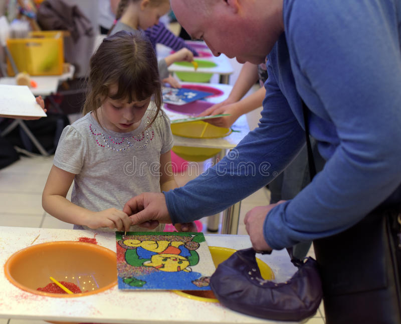 Het kind maakt een beeld uit het zand royalty-vrije stock afbeelding