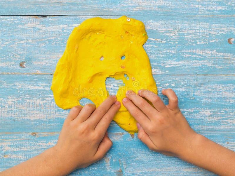 Het kind maakt een mond voor een mok geel slijm op een houten lijst royalty-vrije stock afbeeldingen