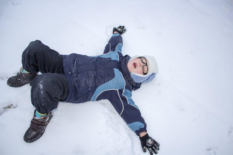 Het kind maakt een sneeuwengel stock afbeeldingen