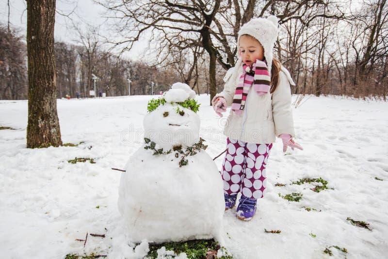 Het kind maakt een Sneeuwman in het Park bij de Winterdag stock foto