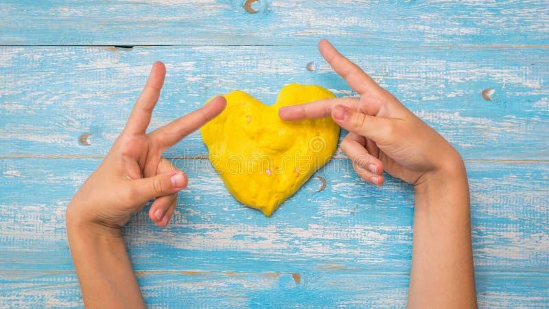 Het kind maakt gebaren met zijn vingers dichtbij het hart van het gele slijm op een houten lijst royalty-vrije stock foto