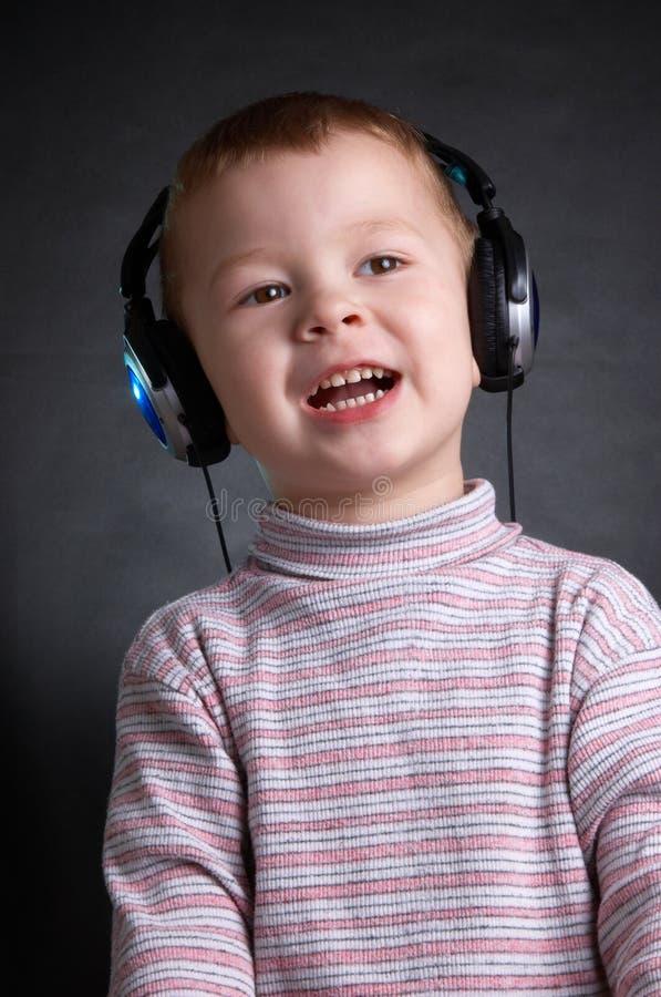 Het kind met oortelefoons royalty-vrije stock afbeelding