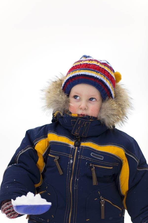 Het kind met schop kijkt omhoog op de winterachtergrond stock foto