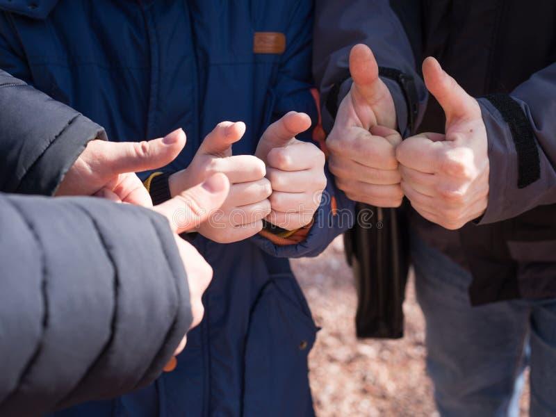 Het kind met tweepersoons tonende duimen ondertekent omhoog, teamconcept royalty-vrije stock afbeeldingen