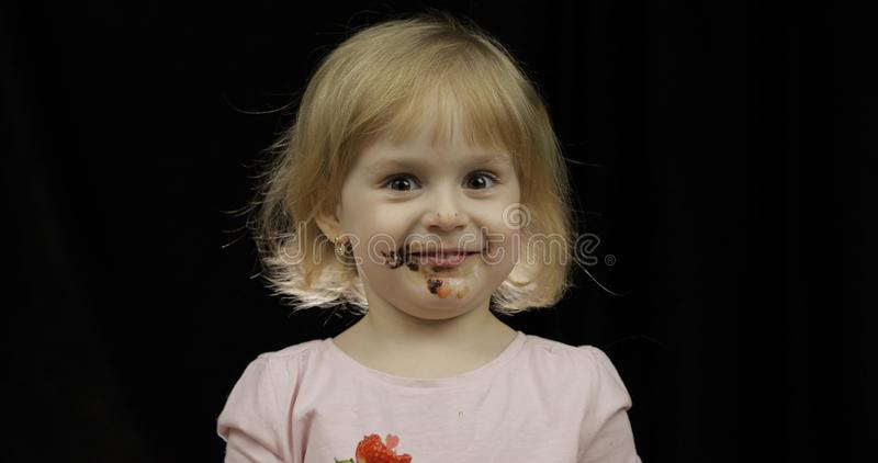 Het kind met vuil gezicht van gesmolten chocolade en slagroom eet aardbei stock foto