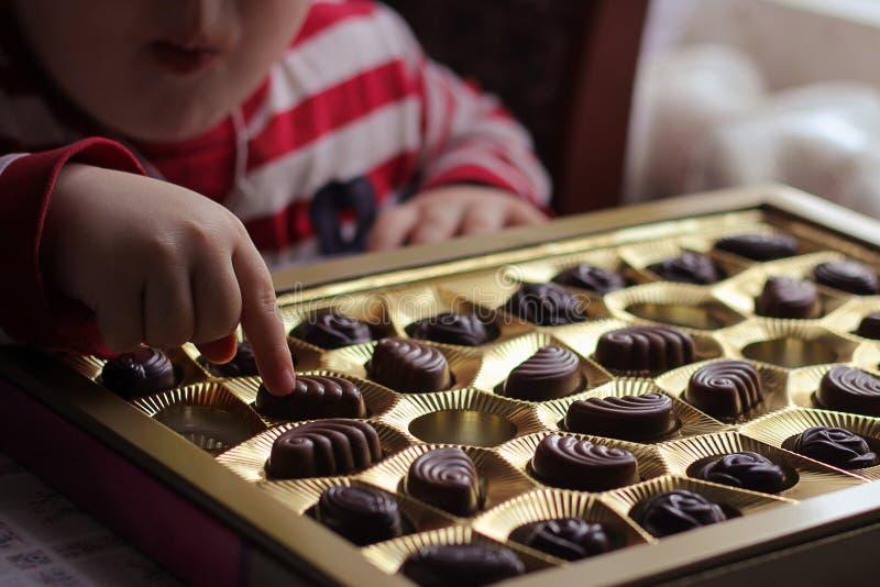 het kind neemt suikergoed het kind eet suikergoed en wil meer stock afbeeldingen