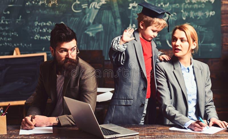 Het kind onderwijst vrouw en de mens in school Kind in grote kostuumlaag en graduatie GLB samen met familie bij bureau, onderzoek stock fotografie