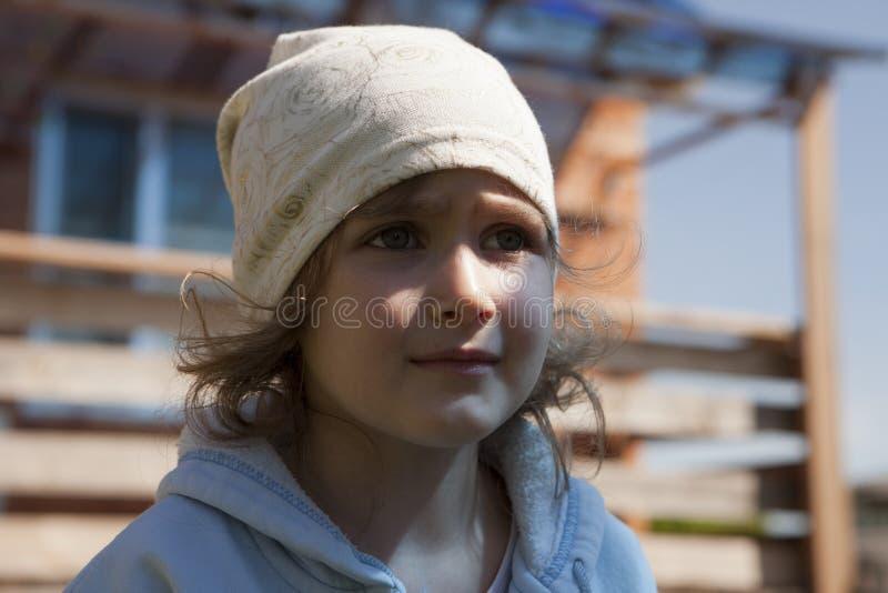 Het kind onderzoekt de afstand met verwachting, hoop of wanhoop Een wit meisje bekijkt angstig iets stock fotografie