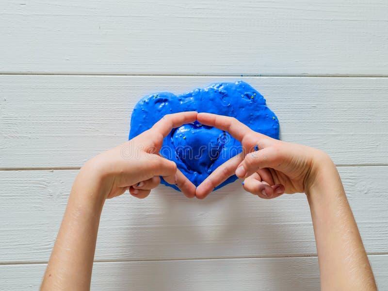 Het kind overhandigt toont hart van over blauw slijm stock foto