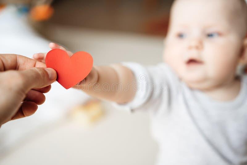 Het kind rekt en neemt het symbool van een rood hart in de hand uit stock foto