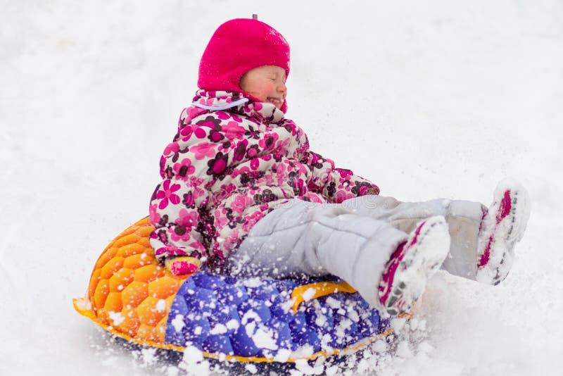 Het kind rolt sneeuwheuvel naar beneden De sport van de winter stock afbeelding