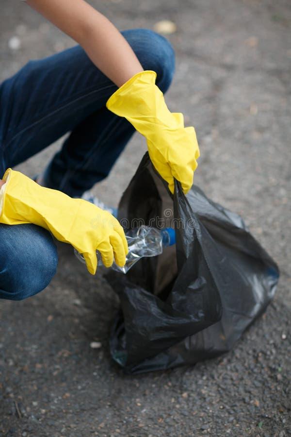 Het kind ` s dient gele latexhandschoenen in houdend een zwarte vuilniszak op een asfaltachtergrond Het concept van de ecologiebe royalty-vrije stock foto's