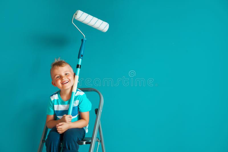 Het kind schildert de blauwe muur met een rol De jongen houdt La stock foto's