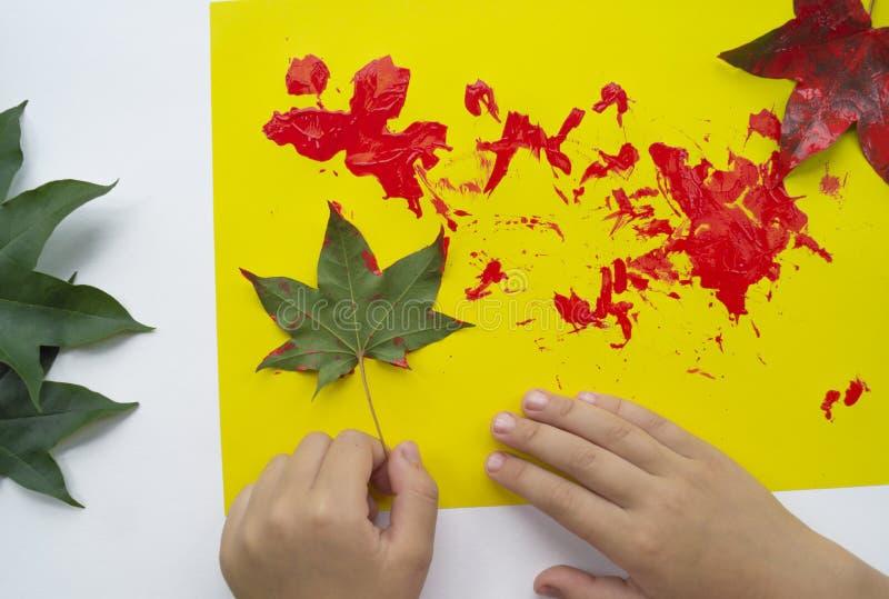 Het kind schildert een beeld van de herfstblad met verven royalty-vrije stock afbeeldingen