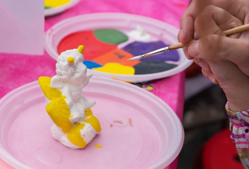 Het kind schildert een ceramisch beeldje met heldere kleuren Ceramische staruette voor het kleuren stock afbeelding