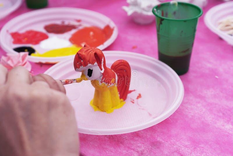 Het kind schildert een ceramisch beeldje met heldere kleuren Ceramische staruette voor het kleuren stock fotografie