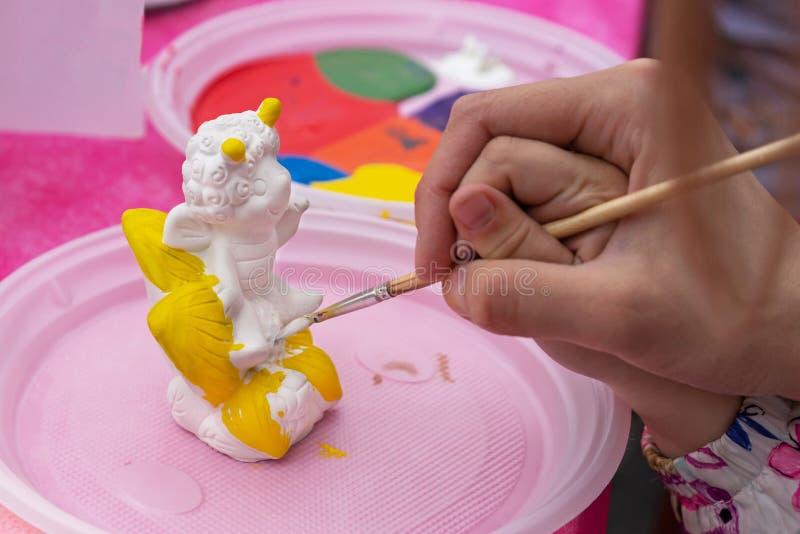 Het kind schildert een ceramisch beeldje met heldere kleuren Ceramische staruette voor het kleuren royalty-vrije stock fotografie