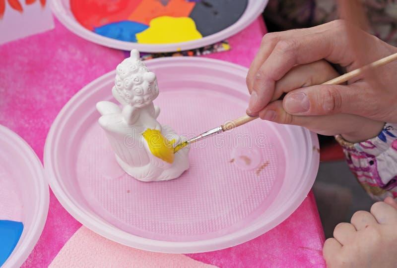Het kind schildert een ceramisch beeldje met heldere kleuren Ceramische staruette voor het kleuren royalty-vrije stock foto