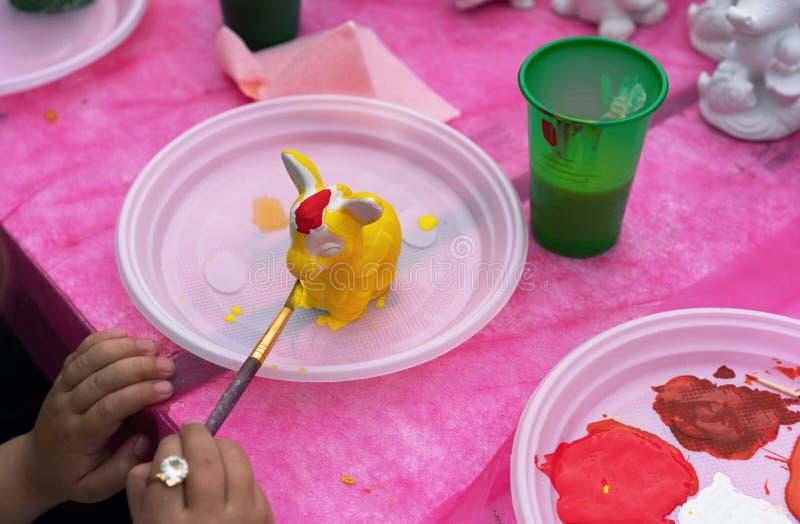 Het kind schildert een ceramisch beeldje met heldere kleuren Ceramische staruette voor het kleuren royalty-vrije stock afbeelding