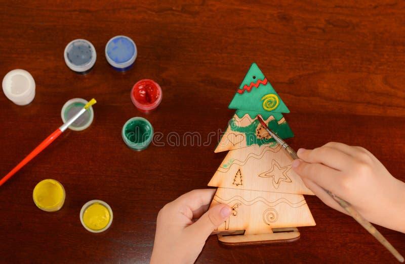 Het kind schildert een houten Nieuwjaarkerstboom Weinig jongen trekt een nieuw-jaarboom stock foto's