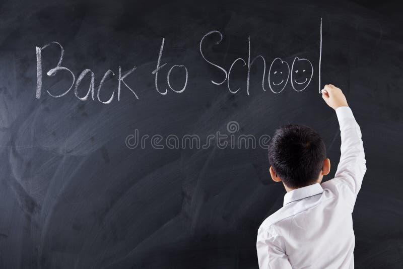Het kind schrijft tekst terug naar School in klasse royalty-vrije stock afbeeldingen