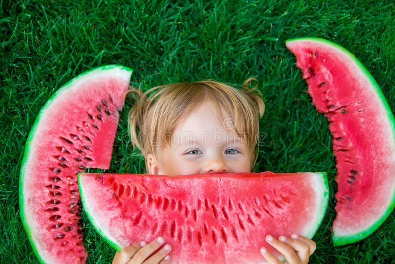 Het kind sluit haar lippen door plak van watermeloen, liggend op het gras in de zomer gelukkig stock fotografie