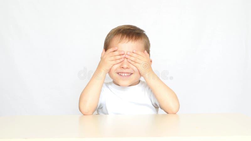 Het kind sluit zijn ogen met van hem indient anticiperen van heerlijke chips - 2 Het kind wordt gediend een plaat met royalty-vrije stock afbeelding