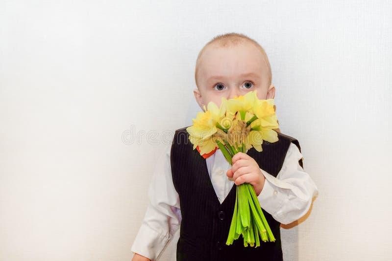 Het kind snuift gele gele narcissen royalty-vrije stock afbeelding
