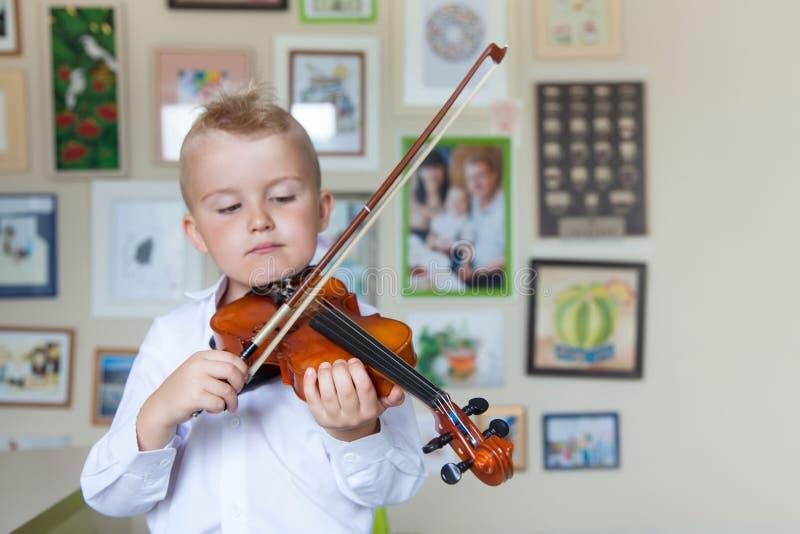 Het kind speelt de viool Jongen die muziek bestuderen royalty-vrije stock foto