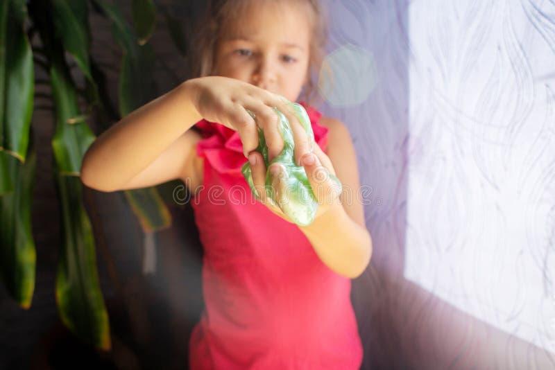 Het kind speelt met toffee een slijm van groene kleur De handen sluiten omhoog stock fotografie
