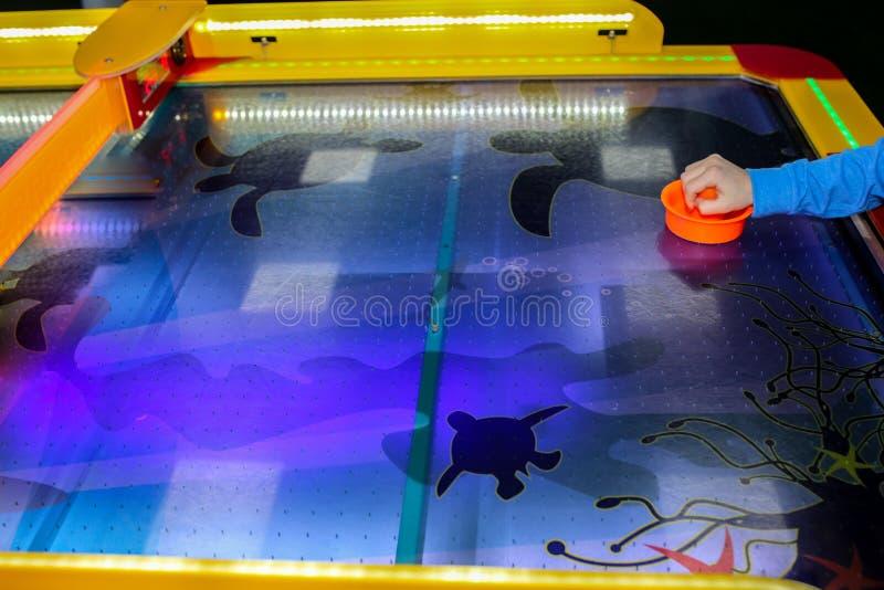 Het kind speelt het spel van het luchthockey en houdt striker Houten hamers en puck in handen Violette lijst met patroon Spel in  royalty-vrije stock foto's