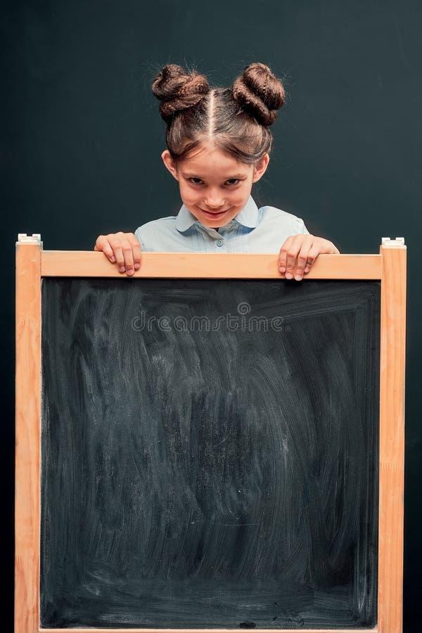 Het kind toont een teken van goedkeuring die zich bij de schoolraad bevinden positief schoolmeisje dat uit van achter een zwarte  stock afbeeldingen