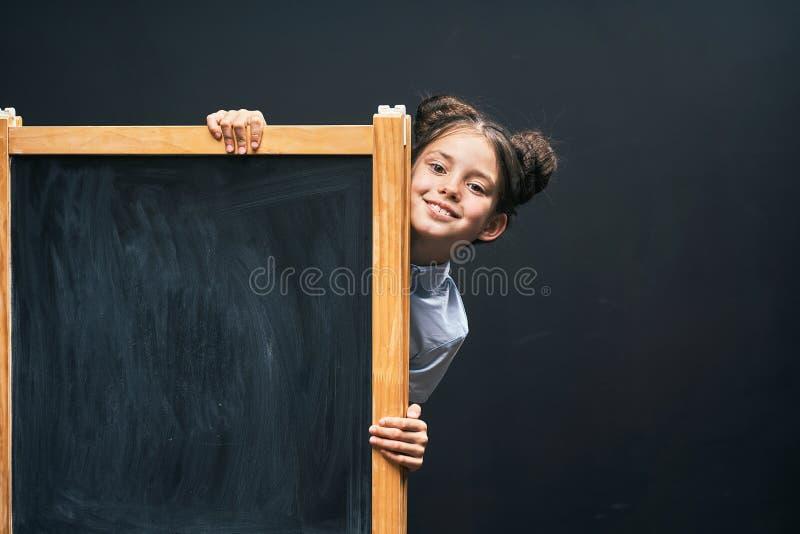 Het kind toont een teken van goedkeuring die zich bij de schoolraad bevinden positief schoolmeisje die uit van achter een zwarte  royalty-vrije stock fotografie