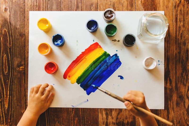 Het kind trekt gouacheverf op een regenboogblad van document stock afbeeldingen
