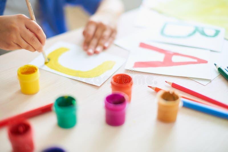 Het kind trekt met de verven van een borstelwaterverf op papier de brief C stock afbeelding