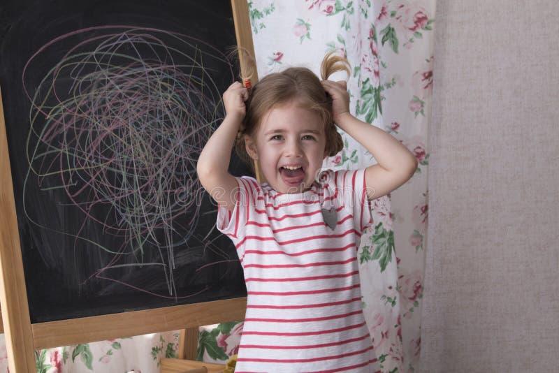 Het kind trekt met stukken van kleurenkrijt op het schoolbord Het meisje drukt creativiteit uit en bekijkt de camera stock foto's