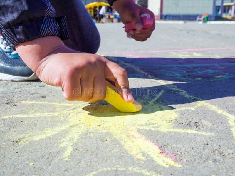 Het kind trekt op het asfalt de zon stock fotografie