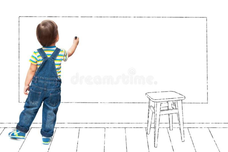 Het kind trekt op een muur in de school stock afbeeldingen