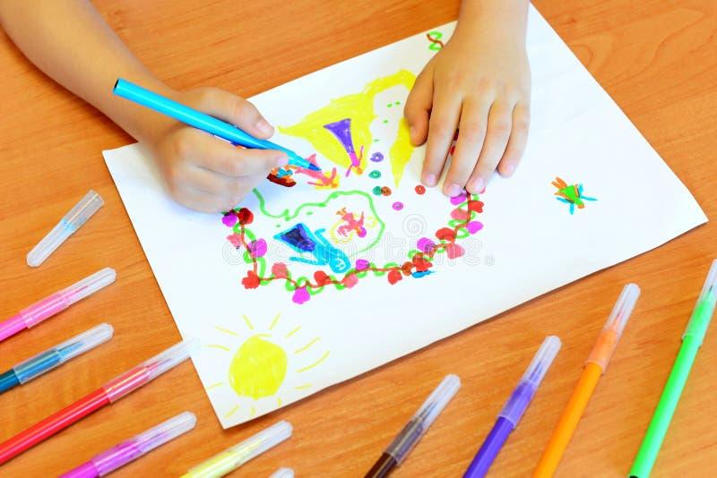 Het kind trekt viltpennen Het kleine kind houdt een blauwe viltpen in hand en trekt abstract prinsessenkasteel royalty-vrije stock afbeeldingen