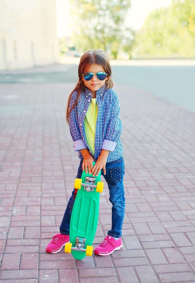 Het kind van het maniermeisje met skateboard die zonnebril en geruit hipsteroverhemd dragen stock foto's
