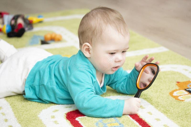 het kind van 7 maanden onderzoekt zich die in een spiegel op tapijt liggen Het meisje van de babyjongen het spelen met spiegel De stock foto's