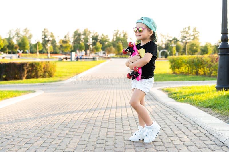 Het kind van het maniermeisje met skateboard dragen zonnebril en hipster overhemd royalty-vrije stock afbeeldingen