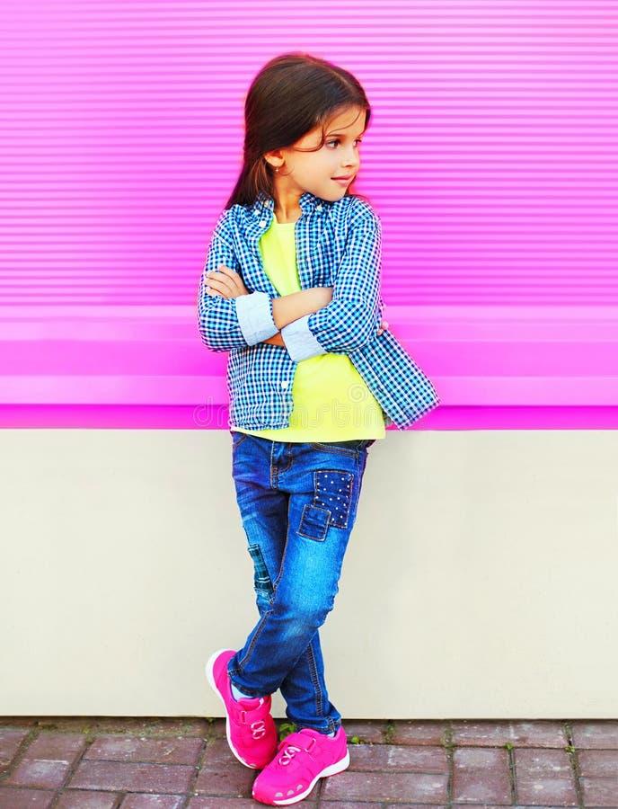 Het kind van het maniermeisje het stellen op stadsstraat op kleurrijke roze muur royalty-vrije stock afbeeldingen