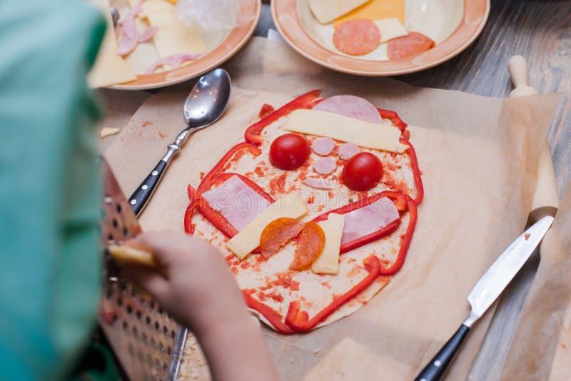 Het kind verfraait de grappige die pizza - peper, kaas, worst, saus uit op het deeg wordt uitgespreid royalty-vrije stock afbeelding