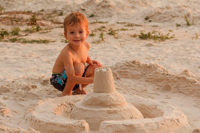 Het kind vernietigt zandkasteel stock foto's