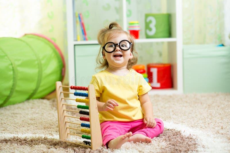 Het kind weared glazen spelend met telraam stock foto