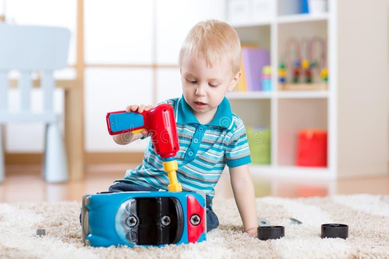 Het kind weinig jongen herstelt stuk speelgoed auto binnen stock afbeelding
