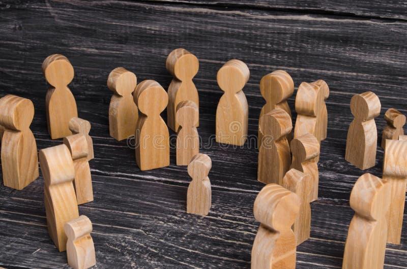 Het kind werd verloren in de menigte Een menigte van houten cijfers van mensen omringt een verloren kind Verloren, ouders die jon stock foto