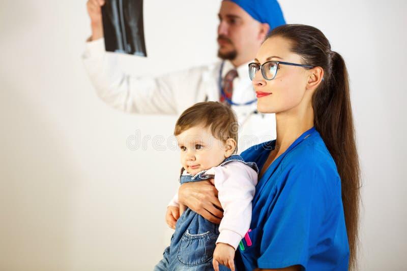 Het kind zit in de handen van de arts, bekijkt de tweede arts de Röntgenstraal Witte achtergrond stock afbeeldingen